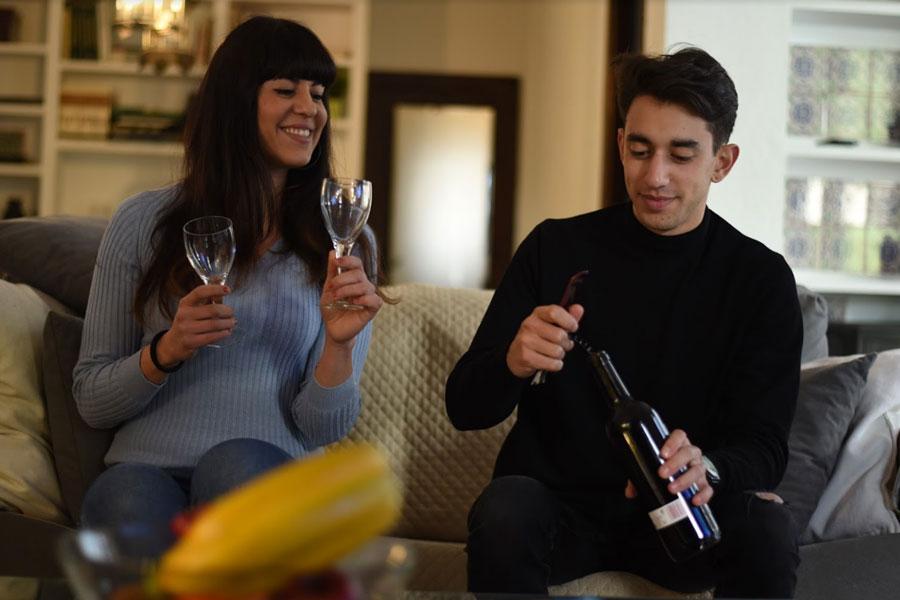 Dos huéspedes abriendo una botella de vino en una casa de alquiler de viviendas turísticas a través de Airbnb